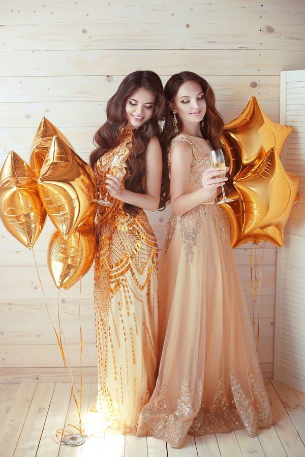 Kvinnor damtoalett Gladlynta flickor som klirrar exponeringsglas av champagne på t royaltyfri bild