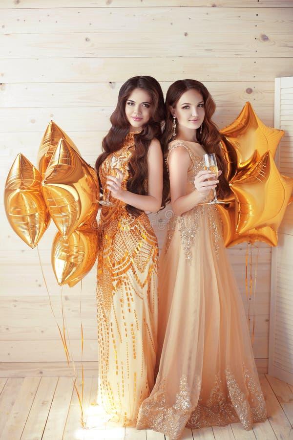 Kvinnor damtoalett Gladlynta flickor som klirrar exponeringsglas av champagne på t royaltyfria foton