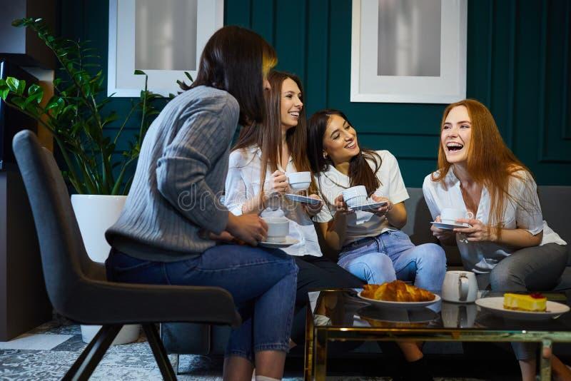 Kvinnor dricker kaffe som hemma skrattar på ett möte av vänner fotografering för bildbyråer
