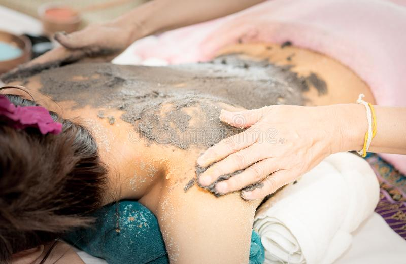 Kvinnor får lera skurar på baksida i Spa arkivfoton