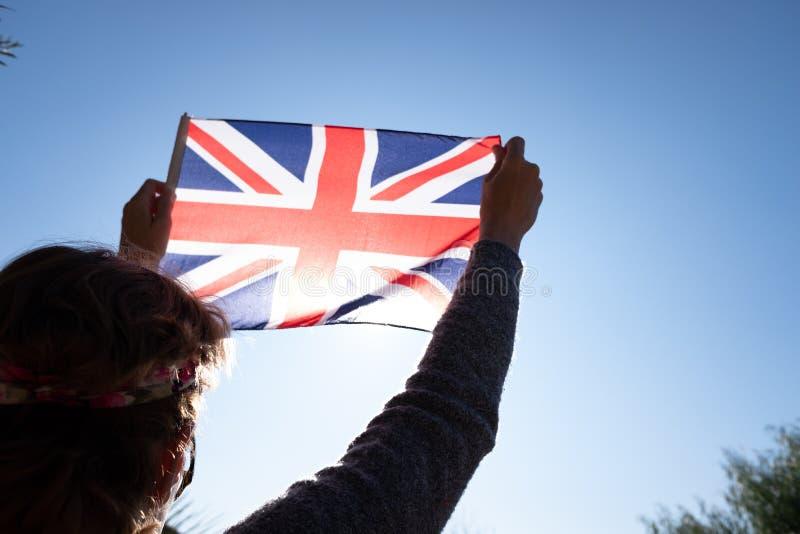 Kvinnor för brittisk flagg mot solen i ett patriotiskt ögonblick royaltyfri bild
