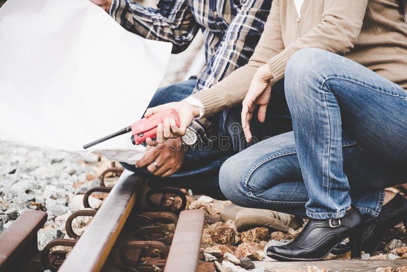 Kvinnor för järnvägtekniker med arbetare rymmer den blåa halv liter- och vithjälmen som kontrollerar järnvägar för borgerlig och  royaltyfria bilder