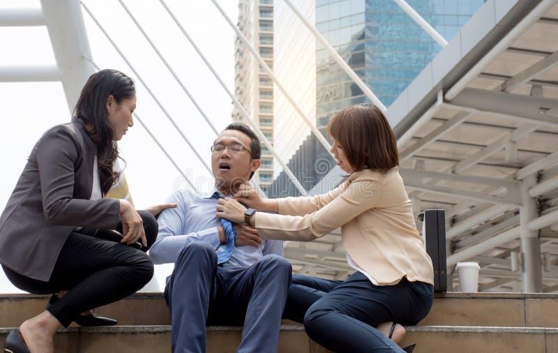 Kvinnor försöker att hjälpa hennes vän som har den stränga bröstkorgen att smärta som hjärtinfarkt i stadsbakgrunden royaltyfria foton