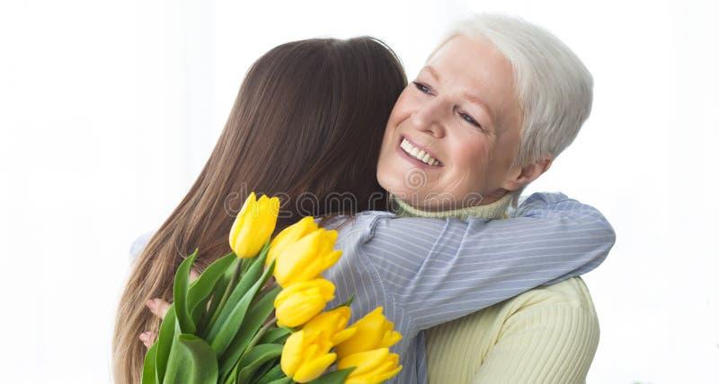 kvinnor f?r dag s Dotter som hälsar hennes moder som ger blommor fotografering för bildbyråer