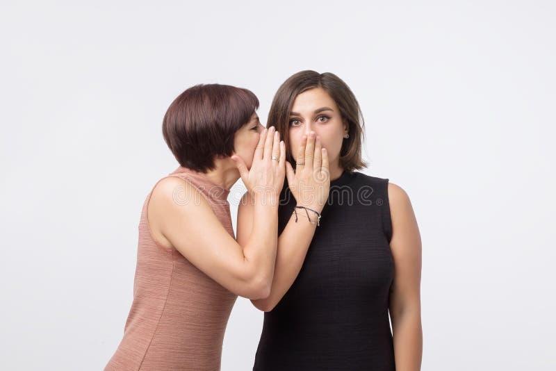 Kvinnor fostrar och dottern som skvallrar och berättar en hemlighet royaltyfria foton