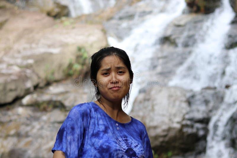 Kvinnor gör roliga framsidor och är bakom vattenfallet royaltyfria foton