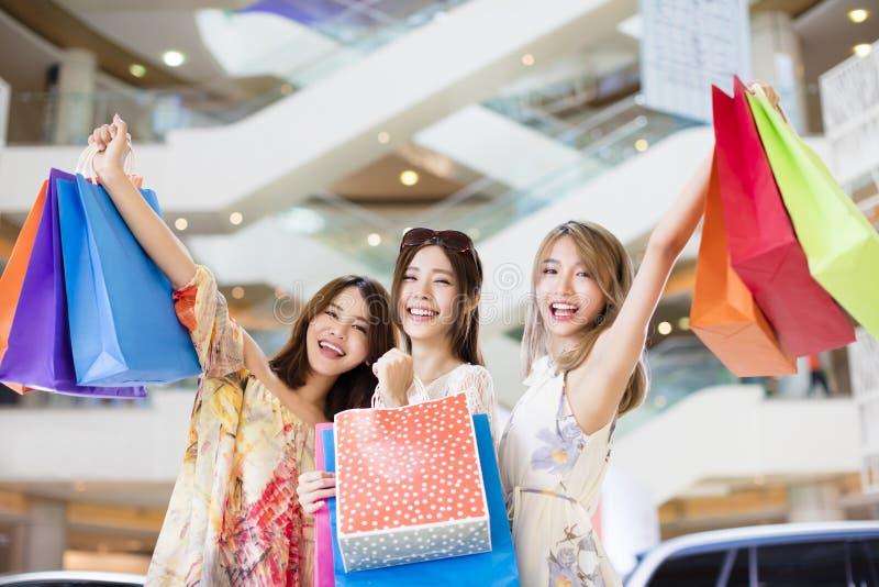 Kvinnor grupperar bärande shoppingpåsar i galleria royaltyfri foto