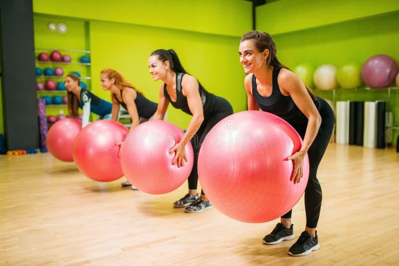 Kvinnor grupperar med stora bollar som gör övningen, kondition arkivbild