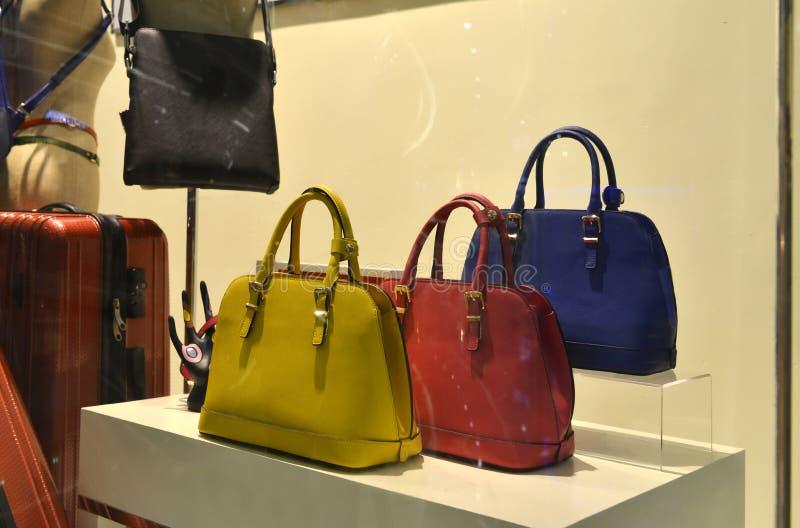 Kvinnor handväska och tillbehör i skärm för modeboutiquefönster, royaltyfria foton