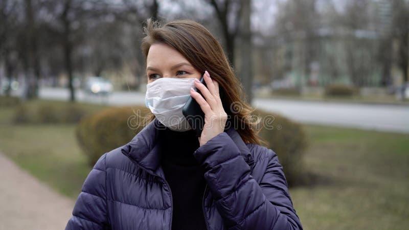 Kvinnor i ansiktsskydd i en stad med mobiltelefon covid-19 coronavirus arkivfoto