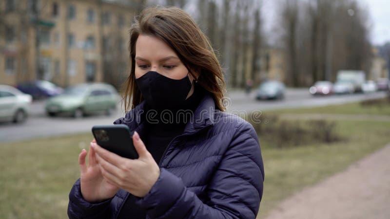 Kvinnor i ansiktsskydd i en stad med mobiltelefon covid-19 coronavirus royaltyfri fotografi