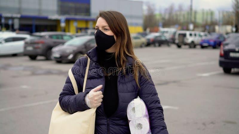 Kvinnor i ansiktsskydd med varor efter stormarknaden covid-19 coronavirus royaltyfria bilder