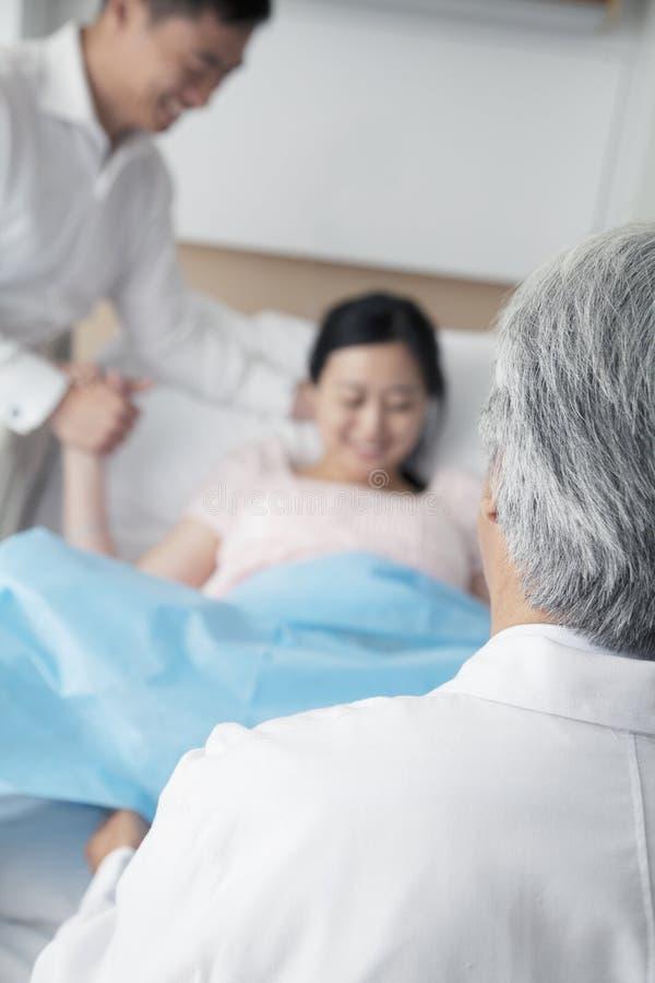 Kvinnor i arbets- innehav hennes makehand med doktorn i förgrunden i sjukhuset royaltyfria foton