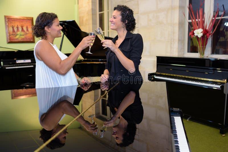 Kvinnor i coctailklänning nära piano som dricker champagne royaltyfri foto