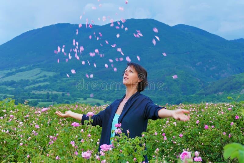 Kvinnor i dalen av rosor kastar kronblad arkivbild