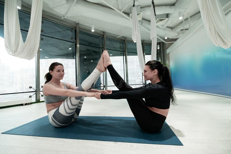Kvinnor i damasker och blast som ler, medan öva yoga arkivfoton
