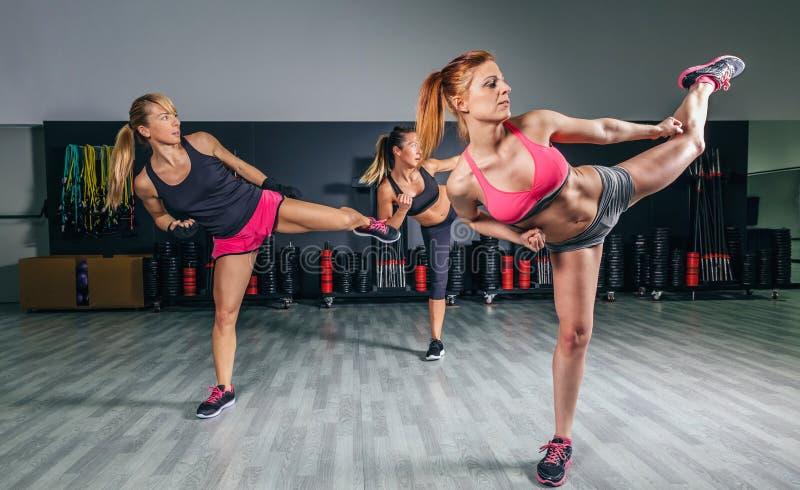 Kvinnor i en boxninggrupp som utbildar hög spark royaltyfria bilder