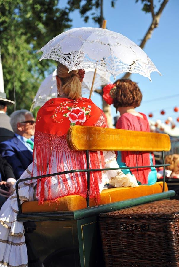 Kvinnor i en hästvagn, Seville mässa, Andalusia, Spanien royaltyfria bilder