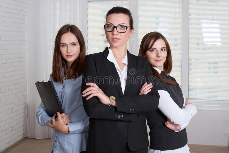 Kvinnor i formell kläder är av olika höjder med hans armar c arkivbild
