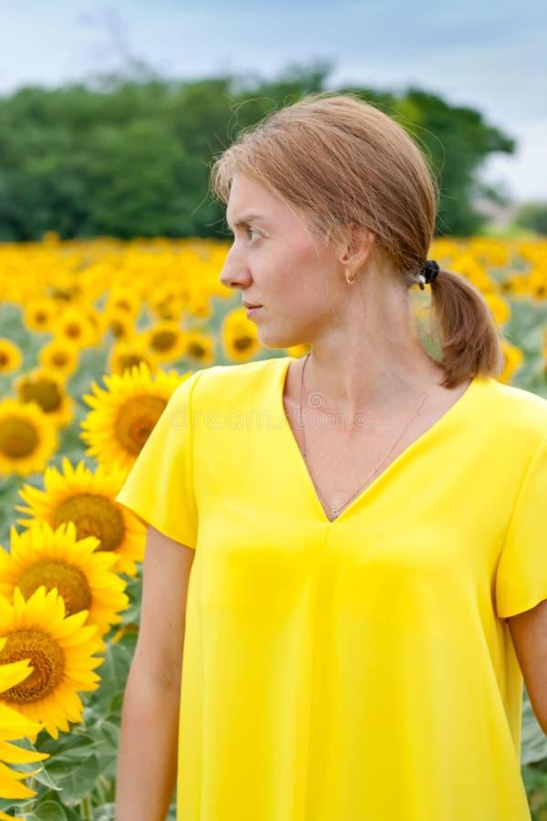 Kvinnor i gul klänning i solrosfält royaltyfri fotografi