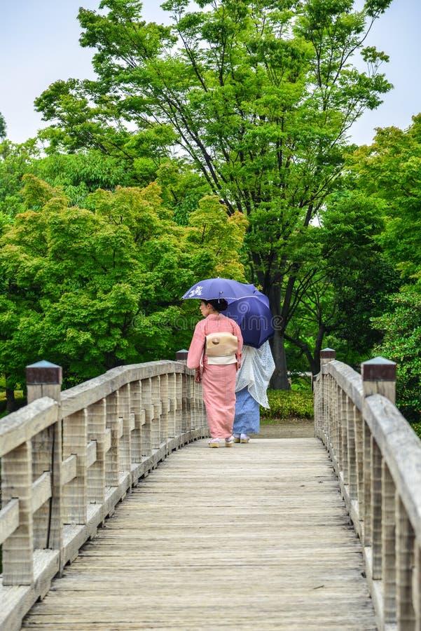 Kvinnor i kimono som går på träbron royaltyfria bilder