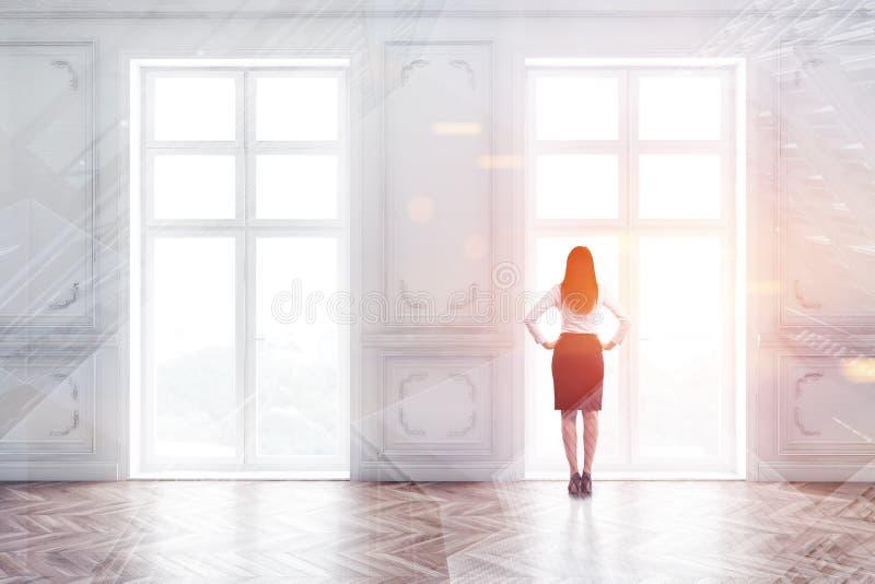 Kvinnor i klädsel i ett tomt rum med fönster arkivbild