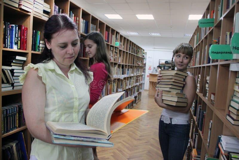 Kvinnor i läseböcker för ett offentligt bibliotek fotografering för bildbyråer