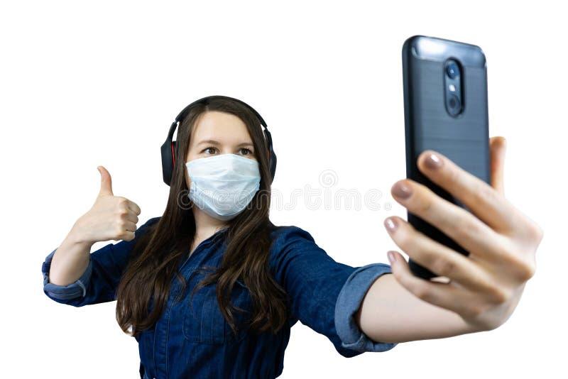 Kvinnor i medicinsk mask som ringer från hemmet under isolering och karantän vid corona virus, covid 19 royaltyfri foto