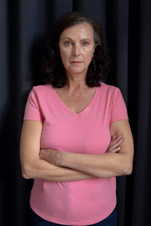 kvinnor i rosa färger för bröstcancer korsar deras armar arkivfoto