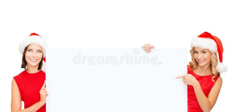 Kvinnor i santa hjälpredahatt med det tomma vita brädet arkivfoton