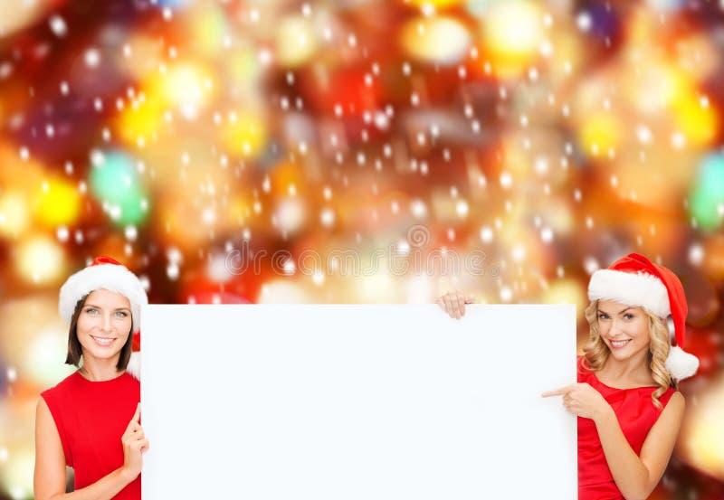Kvinnor i santa hjälpredahattar med det tomma vita brädet arkivfoton