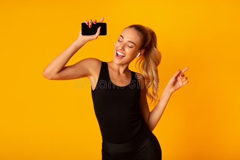 Kvinnor i trådlösa jordbuds med smartphone och dancing, Studio Shot arkivfoton