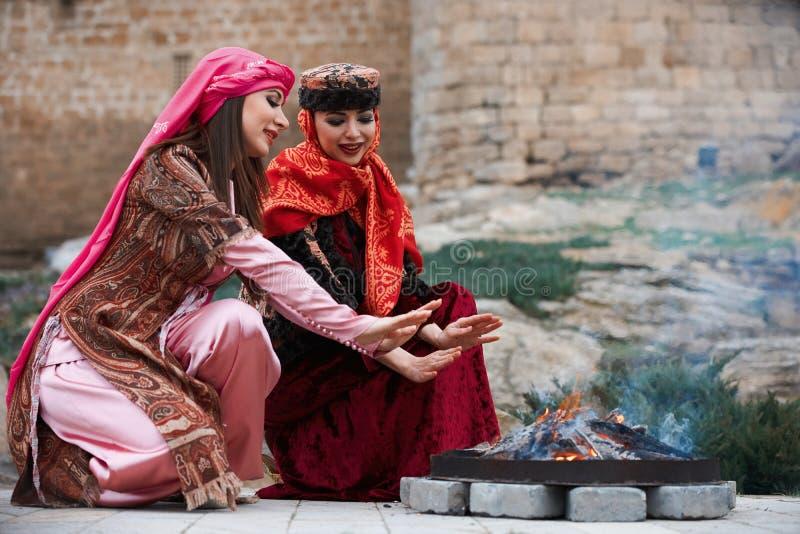 Kvinnor i värmehänder för traditionell azerbajdzjansk klänning ovanför brasan royaltyfria foton