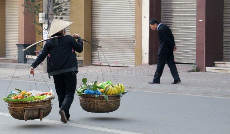 Kvinnor i Vietnam som bär traditionellt triangulärt sugrör, gömma i handflatan hattar arkivbild
