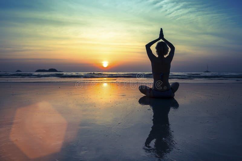 Kvinnor i yogameditation poserar på den fantastiska solnedgången royaltyfria foton