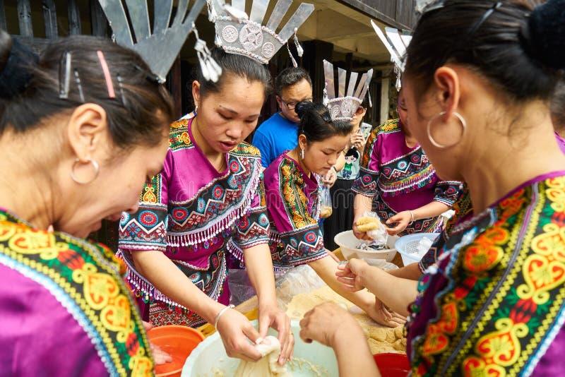 Kvinnor klädde traditionella dräkter som förbereder pastell och sötsaker arkivfoton