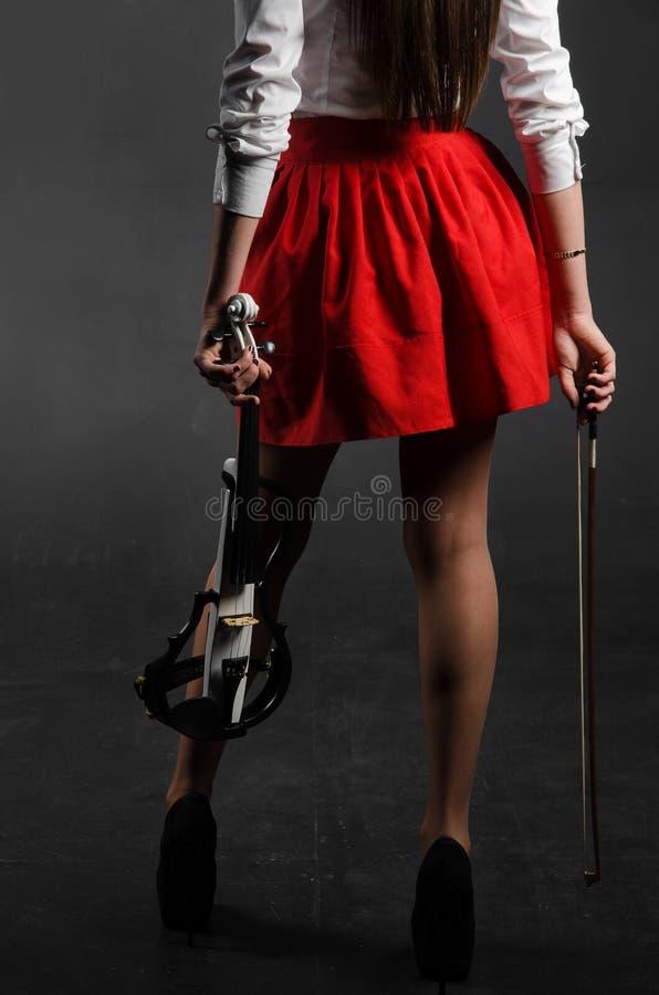 Kvinnor lägger benen på ryggen i en kjol med en fiol arkivbilder