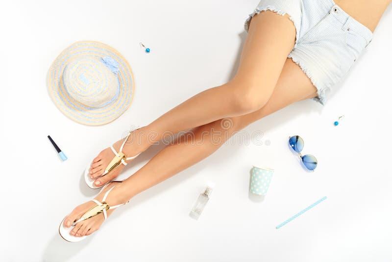 Kvinnor lägger benen på ryggen och den stilfulla tillbehören för sommarmode arkivbilder