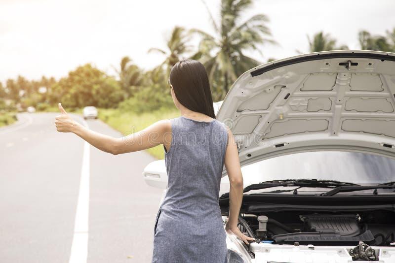 Kvinnor lyfter deras händer för hjälp Bilen är bruten royaltyfria bilder