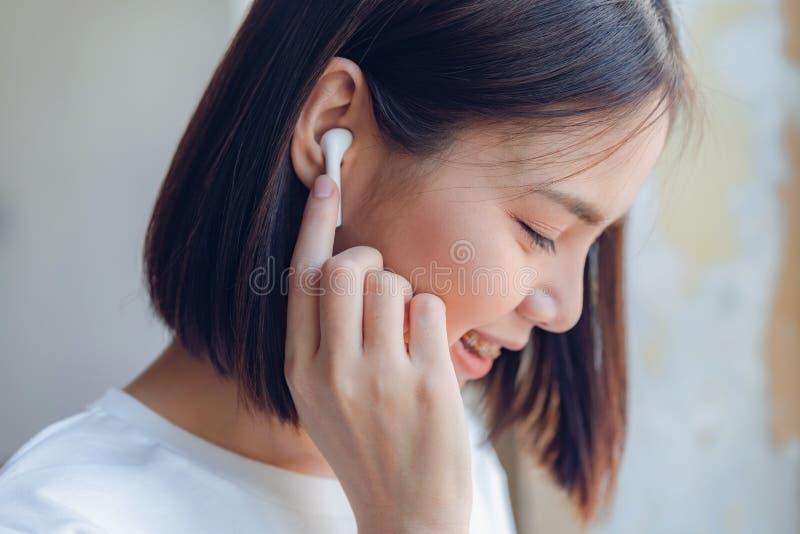 Kvinnor lyssnar till musik fr?n vit h?rlurar Och genom att anv?nda handhandlag f?r att anv?nda olika funktioner, lyckligt lynne royaltyfri foto