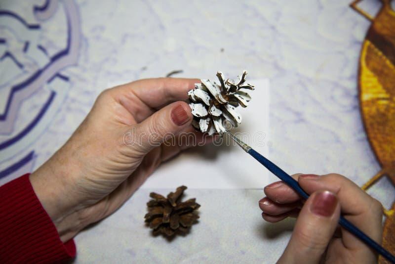 Kvinnor målar en brun lump med vit färg Helgdagar, jul, nyår arkivbild