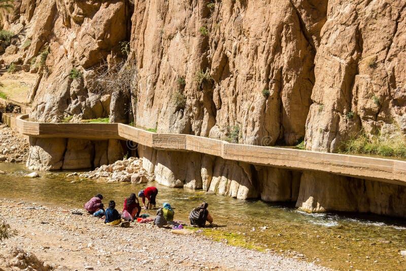 Kvinnor med childrenre som gör tvätterit på den flodTodra klyftan, Marocko royaltyfri fotografi