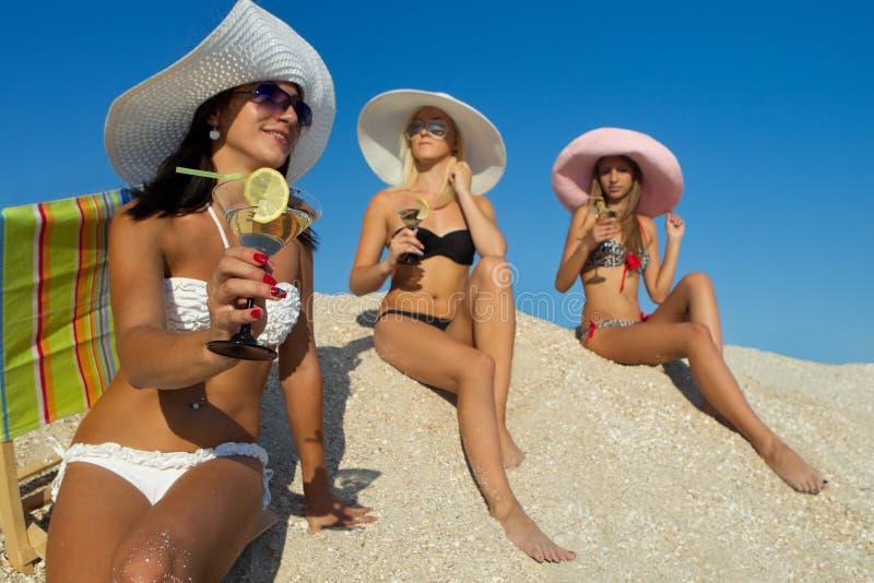Kvinnor med coctailen på strand royaltyfri fotografi