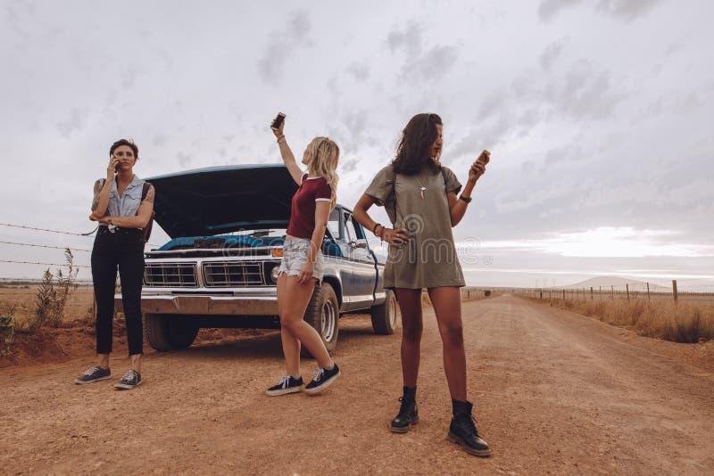 Kvinnor med den brutna ner bilen genom att använda telefoner för hjälp royaltyfri foto