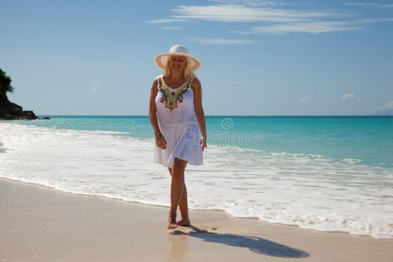 Kvinnor med den vita klänningen på stranden arkivbild