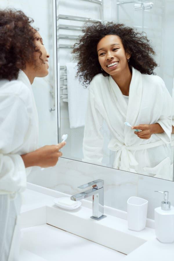 Kvinnor med ett leende och ett skönhetsyta som ser i spegeln på toaletten arkivbild