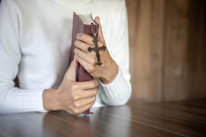 Kvinnor med kors och bibel i händer som ber om gudars välsignelse på morgonen, andlighet och religion arkivfoton