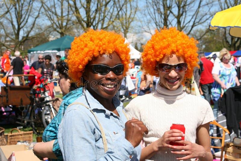 Kvinnor med orange peruker på Kingsday i Amsterdam royaltyfria foton