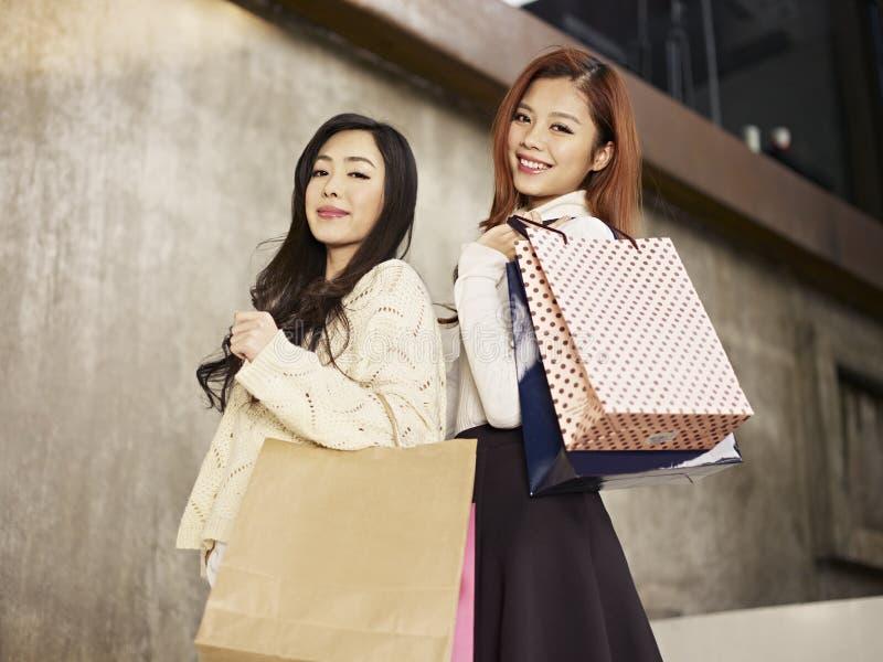 Kvinnor med shoppingpåsar på skuldra royaltyfri fotografi