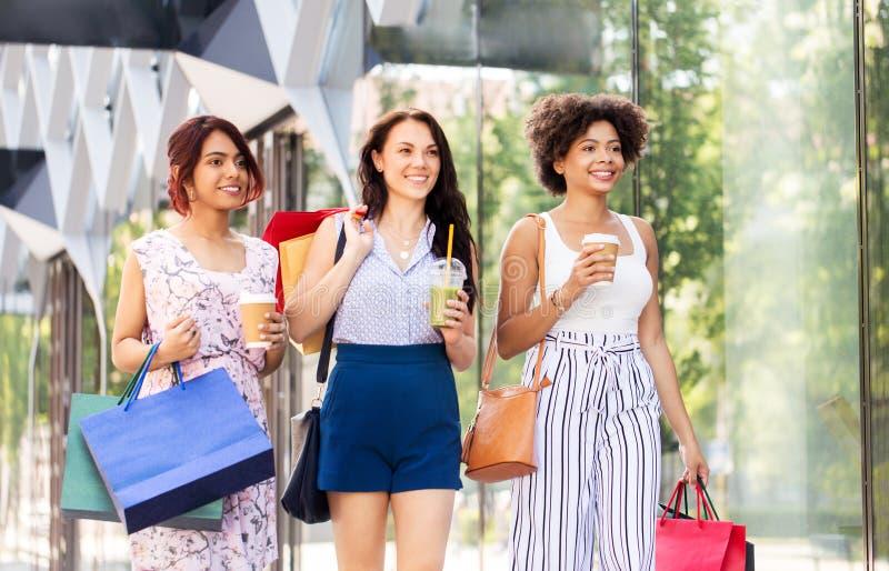 Kvinnor med shoppingp?sar och drinkar i stad royaltyfri fotografi
